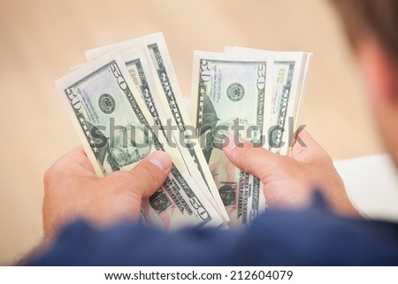 Cropped image of man counting fifty dollar bills at home - stock photo
