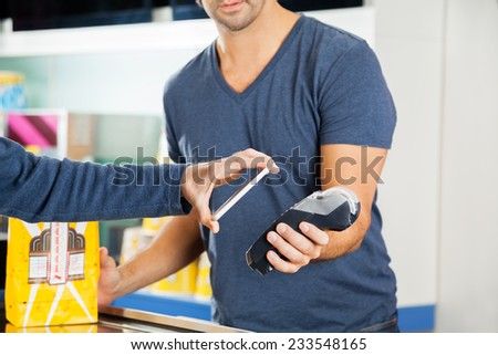 Cropped image of man placing smartphone over credit card reader to make payment at cinema concession stand - stock photo