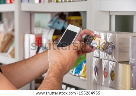 Cropped image of man's hand with cellphone scanning product - stock photo