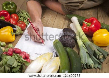 Cropped image of man's hand writing list of organic vegetables on wooden surface - stock photo