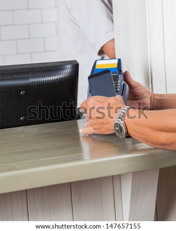 Cropped image of man's hands making payment through cellphone at cash counter - stock photo