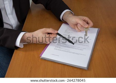 Cropped image of man signing contract with keys on it