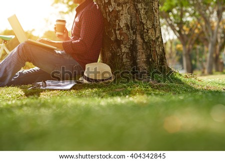 Cropped image of man sitting under the tree with coffee and laptop - stock photo