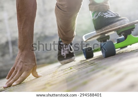 Cropped image of man skateboarding on footpath during summer - stock photo