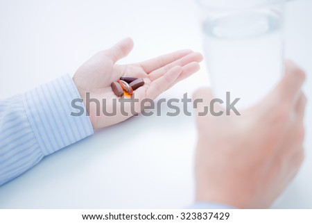 Cropped image of man taking pills with glass of water
