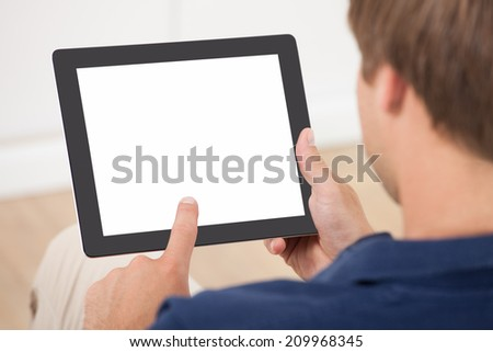 Cropped image of man using digital tablet with blank screen at home - stock photo