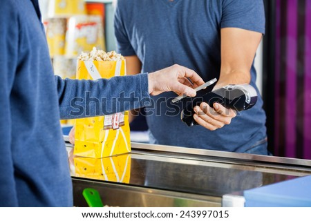 Cropped image of man using NFC technology to make payment at popcorn counter at cinema - stock photo