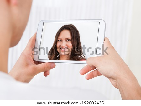 Cropped image of man video conferencing with woman on digital tablet at home - stock photo
