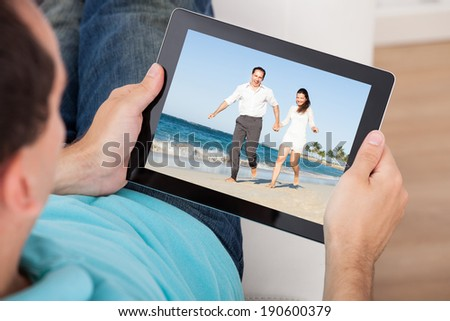 Cropped image of man watching movie on digital tablet at home - stock photo