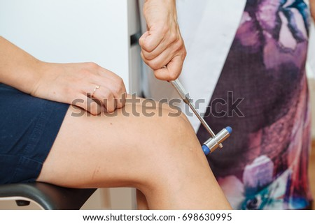 Cropped image of neurologist testing knee reflex on a female patient using a hammer