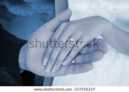 Cropped image of newly wed couple holding hands against large moon over city - stock photo