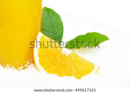 Cropped image of orange juice with ice cubes and orange fruit with citrus leaves on ice on white background - stock photo