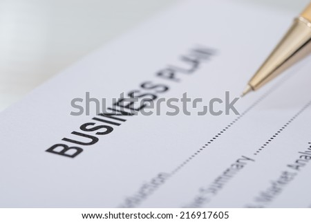 Cropped image of pen business plan form on desk - stock photo