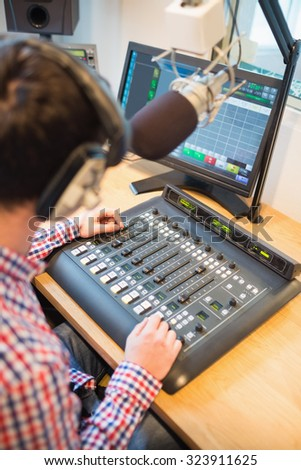 Cropped image of radio host using sound mixer on table in studio - stock photo