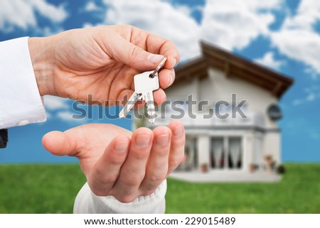 Cropped image of real estate agent giving keys to owner against new house