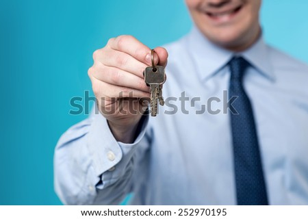 Cropped image of realtor offering a house key - stock photo