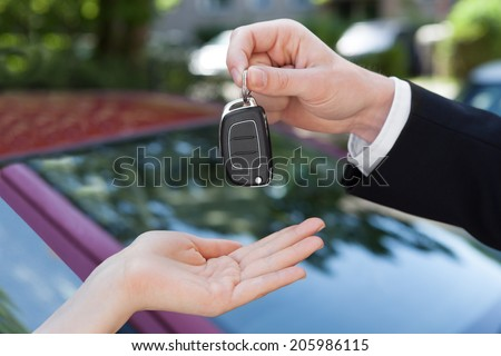 Cropped image of salesman handing key to woman by new car