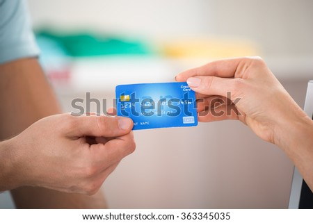 Cropped image of salesman taking credit card from female customer in clothing store - stock photo