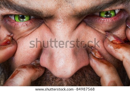 Cropped image of scary man's face with green artificial eyes and bleeding fingers