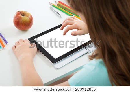 Cropped image of schoolgirl using digital tablet with blank screen at table - stock photo