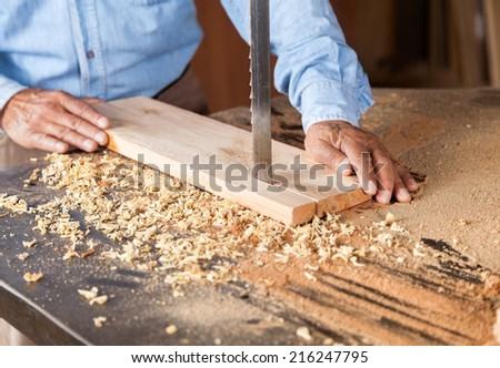 Cropped image of senior carpenter cutting wood with bandsaw in workshop - stock photo