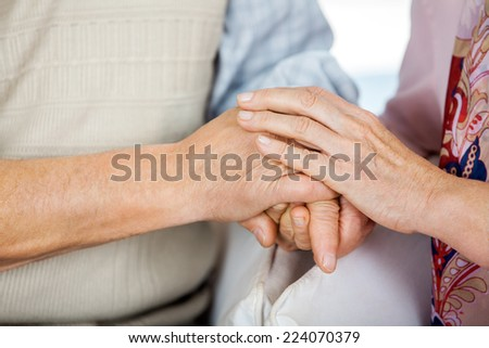 Cropped image of senior couple holding hands while sitting on chairs at nursing home - stock photo