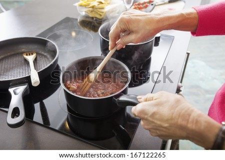 Cropped image of senior woman preparing food at kitchen counter