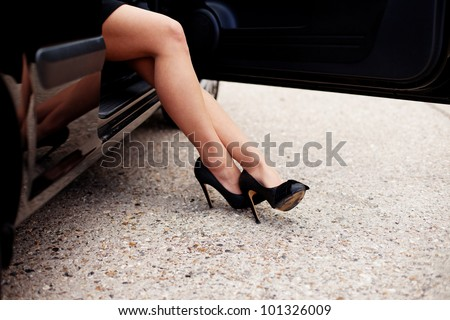 Cropped image of sexy stockinged female legs in fashionable high heeled shoes alighting from a car