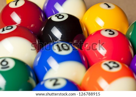 Cropped image of shiny colorful pool balls with number arranged in a row on pool table. - stock photo