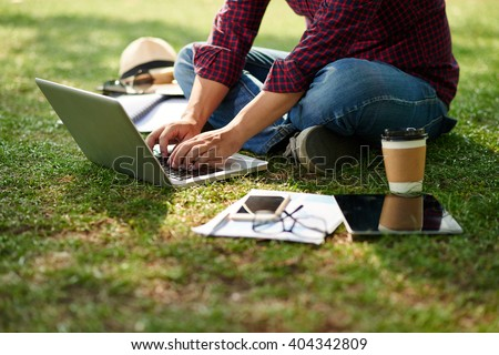 Cropped image of student sitting on the ground and working on laptop - stock photo