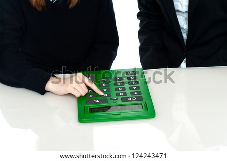Cropped image of teacher and a student working out on a large green calculator. - stock photo