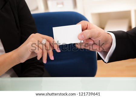 Cropped image of the hands of a business man handing over a blank white business card to a woman ready for your contact information - stock photo