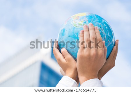Cropped image of the leaders of the company holding a globe miniature in hands in the sign of togetherness  - stock photo