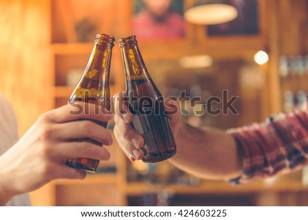 Cropped image of two men clanging bottles of beer together while sitting at bar counter in a modern urban cafe - stock photo