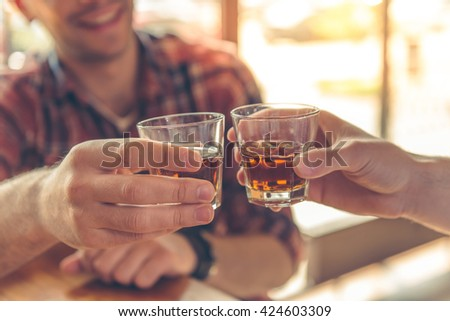 Cropped image of two men clanging glasses of alcoholic beverage together while sitting at bar counter in a modern urban cafe - stock photo
