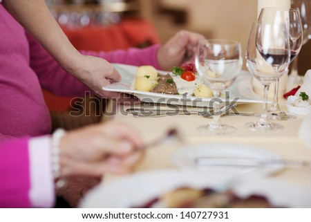 Cropped image of waiter's hand serving dish to customers at restaurant table - stock photo