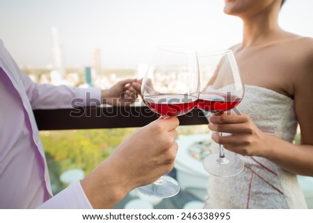 Cropped image of well-dressed couple clinking wine-glasses - stock photo