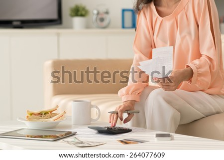 Cropped image of woman calculating unpaid bills: home economics concept