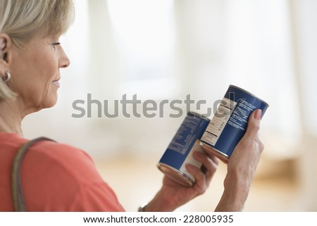 Cropped image of woman comparing products in shop - stock photo