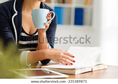 Cropped image of woman drinking coffee and reading a book - stock photo