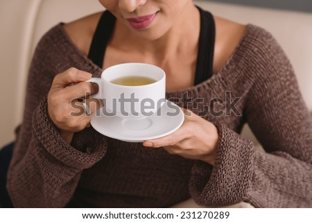 Cropped image of woman drinking tea - stock photo