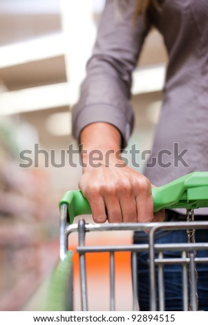 Cropped image of woman holding pushcart at supermarket - stock photo