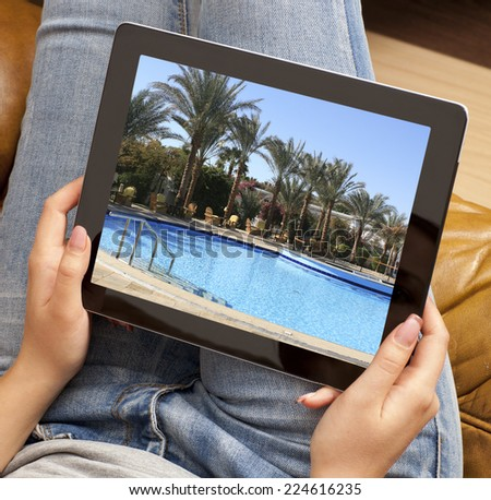 Cropped image of woman looking at resort photo on tablet - stock photo
