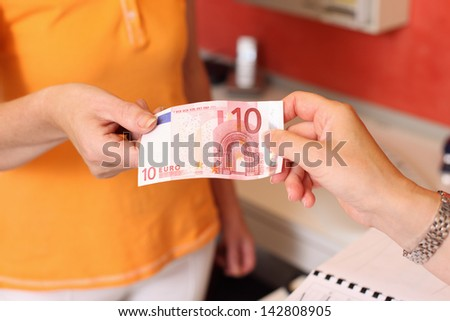Cropped image of woman paying cash to dentist at clinic - stock photo