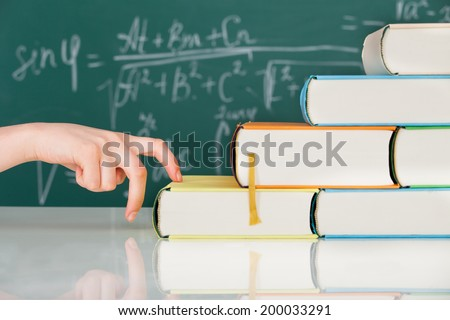 Cropped image of woman's hand climbing stack books in classroom - stock photo