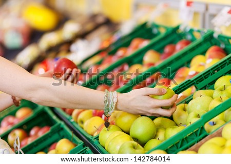 Cropped image of woman's hands choosing apples in grocery store