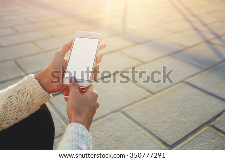 Cropped image of woman's hands holding cell telephone with blank copy space screen for your text message or information content, female reading web page publicity on smart phone while relaxing outside - stock photo