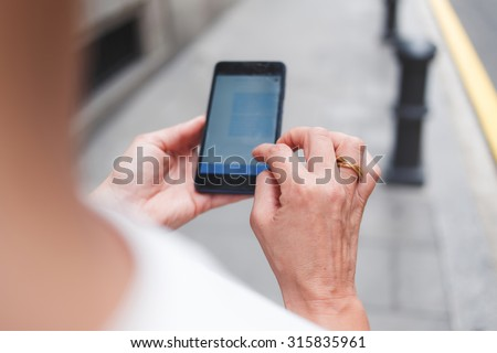 Cropped image of woman's hands holding mobile phone with copy space area for your text message or advertising content, female tourist using cell telephone for navigation while walking on the street - stock photo