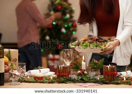 Cropped image of woman serving decorated Christmas table - stock photo