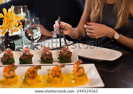 Cropped image of woman taking appetizer with chopsticks, selective focus